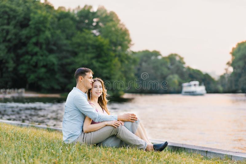 A young couple in love, a guy and a girl are sitting on the shore of the lake, happy and smiling. First date stock image