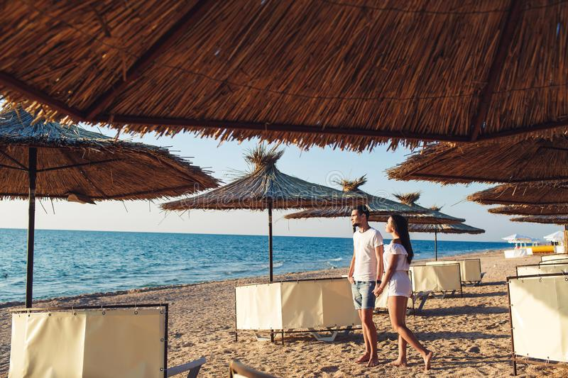 Young couple in love holding hands among reed umbrellas on the sea beach. stock photography