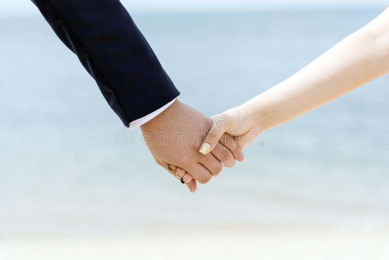 Young couple in love holding hands together while walking on the beach. Lover Concepts stock image