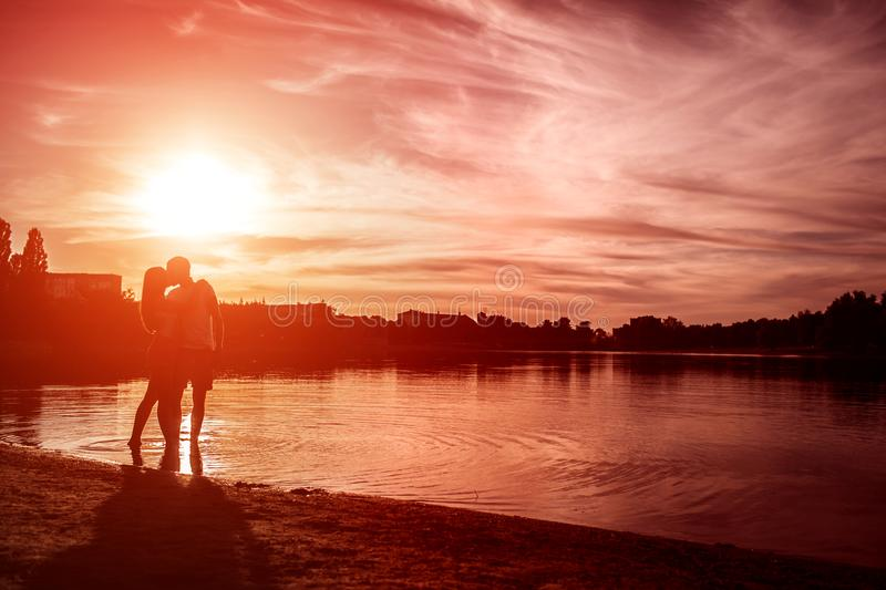 Young couple in love hugging and kissing on summer river bank at sunset. Man and woman having a date royalty free stock photos