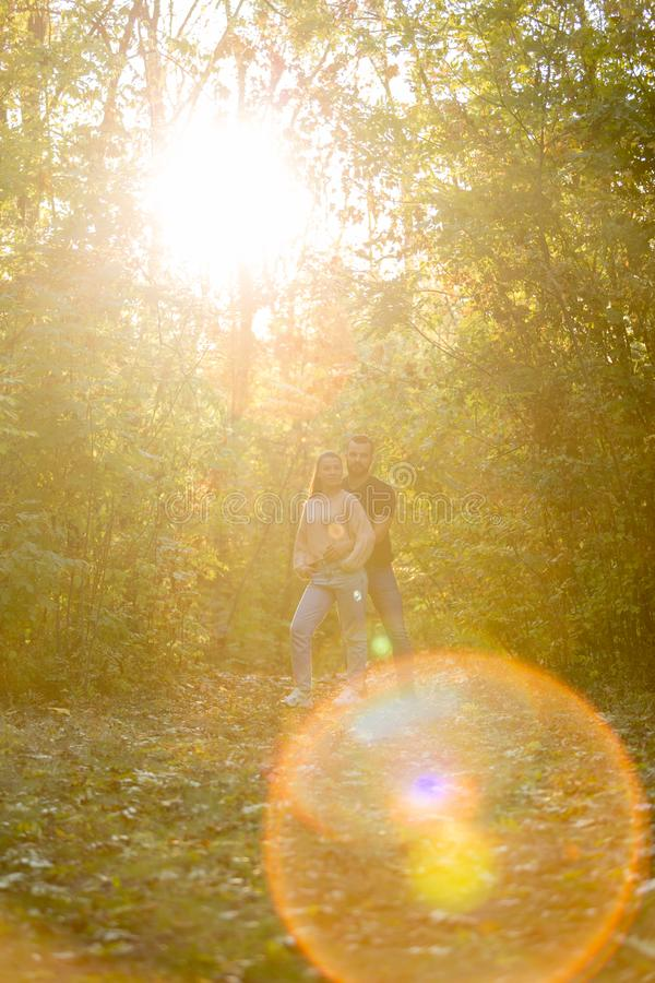 Young couple in love hugging in the Park. Man and woman alone with each other. Warm autumn evening in forest. Rays of the setting stock photography