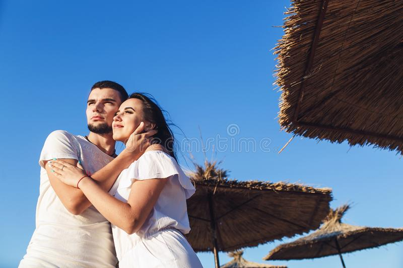 Young couple in love hugging among reed umbrellas on the sea beach. royalty free stock photos