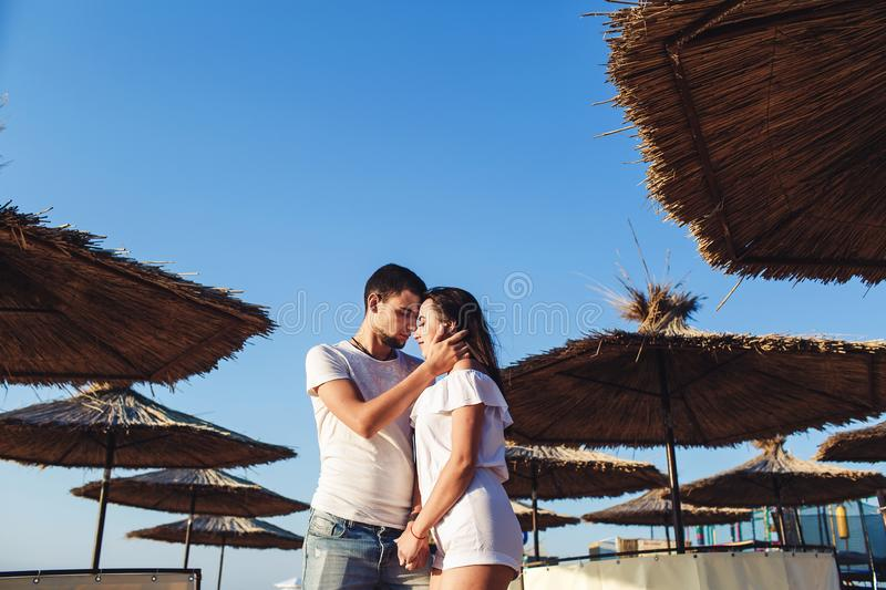 Young couple in love hugging among reed umbrellas on the sea beach. royalty free stock photography