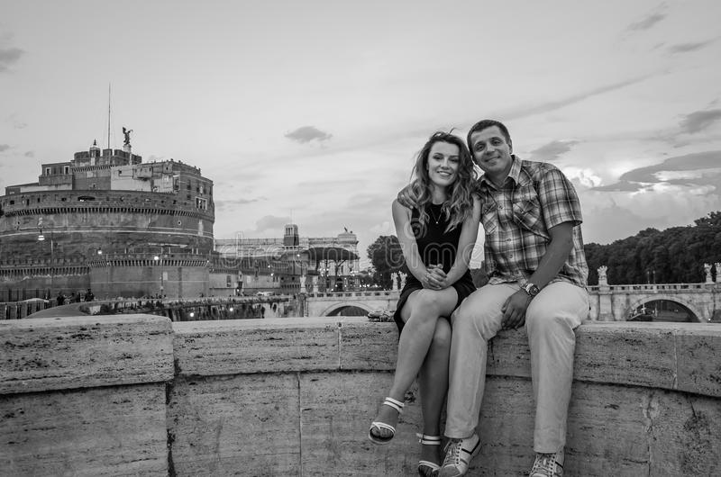 Young couple in love, husband and wife, on the stone bridge of the Tiber River embankment, against the backdrop of the Angel Vatic stock images