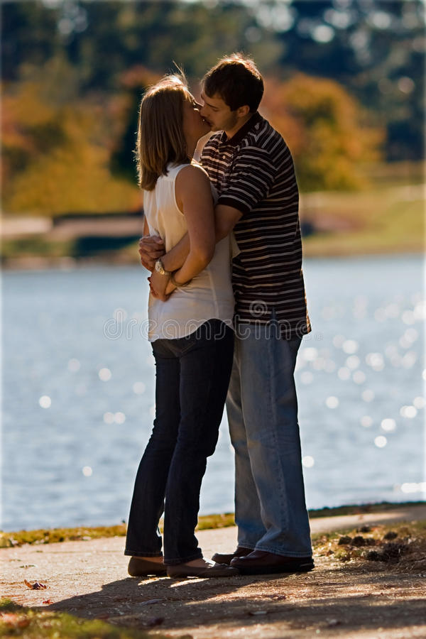 Young Couple In Love Kiss By A Lake