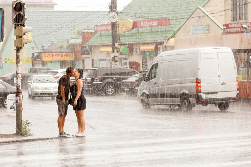 Young couple in love kisses at a traffic light on the roadway not paying attention to heavy rain royalty free stock images