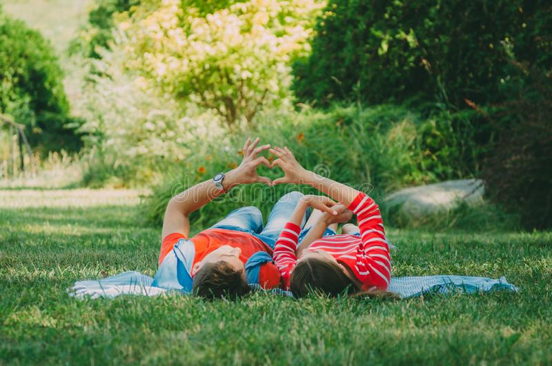 Young couple in love lies on a plaid in the park, make hands a symbol of love - the heart. Picnic for couples in love stock photo