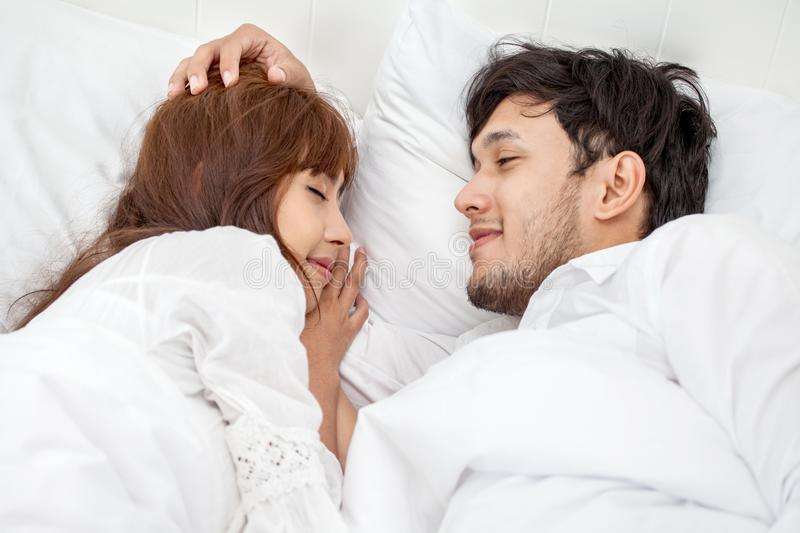 Young couple in love looking at each other lying together on white bed Romantic moment in morning to rub gently on the head royalty free stock photo
