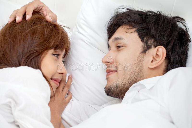 Young couple in love looking at each other lying together on white bed Romantic moment in morning to rub gently on the head stock photography