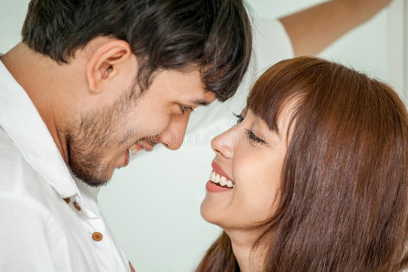 Young couple in love looking to each other. wife helping husband to get dress up in morning romantic moment stock image