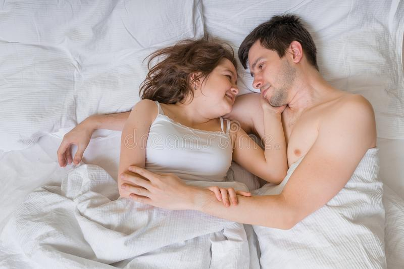 Young couple in love is lying in bed and hugging. They are looking in their eyes royalty free stock image