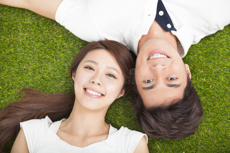 young couple in love lying together on the grass royalty free stock photo