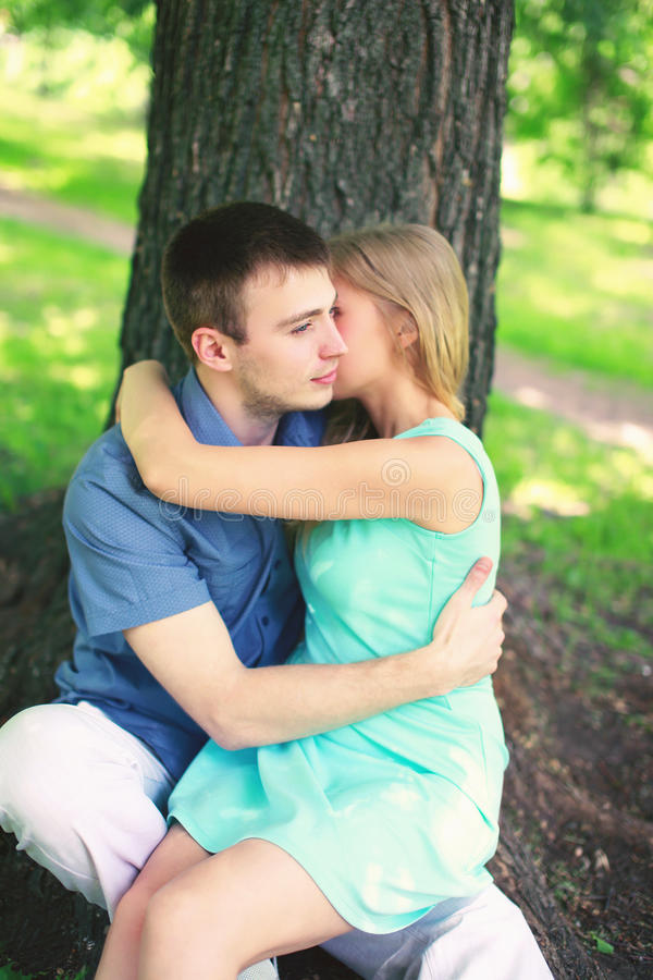 Young couple in love, man and woman resting near tree. Young couple in love, men and women resting near tree sitting in the park together, warm feelings royalty free stock photos