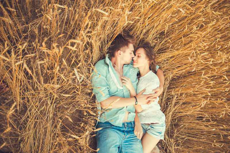Young couple in love outdoor.Couple hugging.Young beautiful couple in love staying and kissing on the field on sunset. royalty free stock image