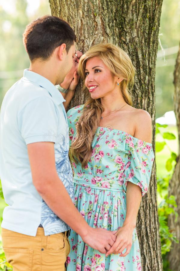 Young couple in love outdoor. Sensual outdoor portrait of young stylish fashion couple posing in summer nature royalty free stock photos