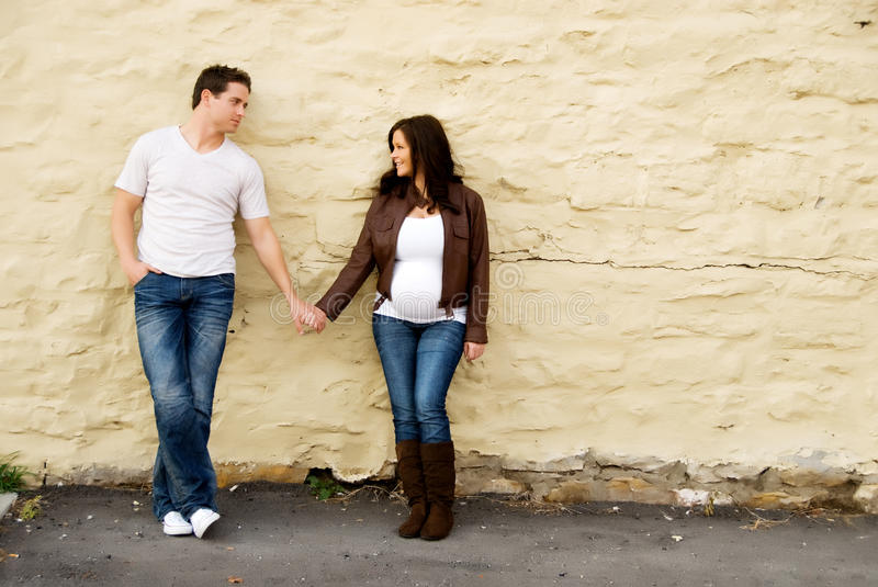 Young Couple in Love and pregnant. A maternity portrait of a man and a woman at nine months along in her pregnancy holding hands stock photography