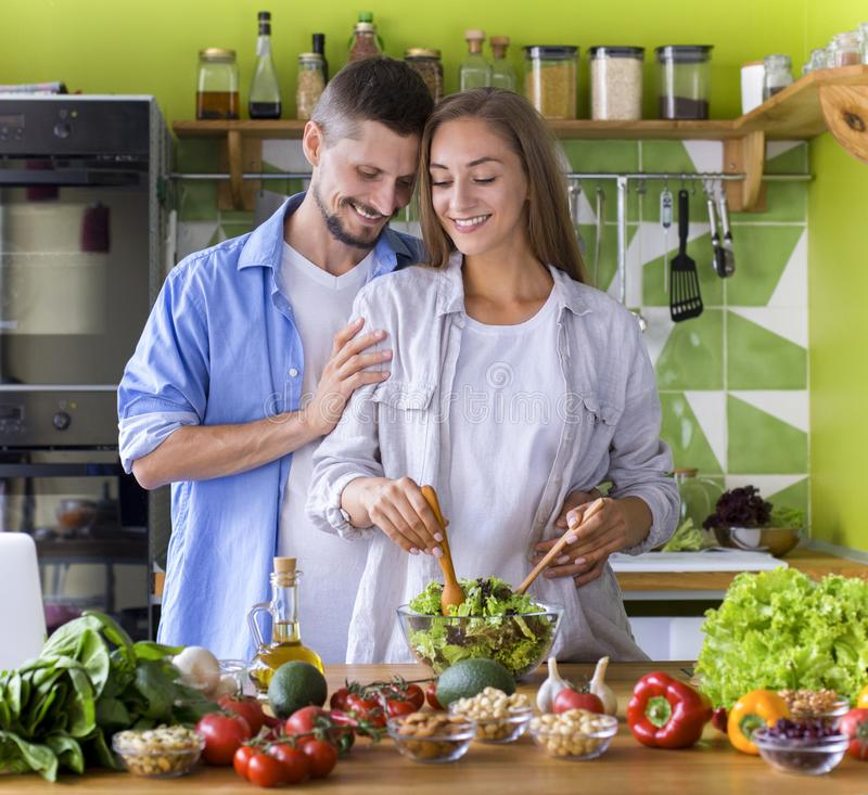 Young couple in love preparing tasty vegetarian dinner together stock photography