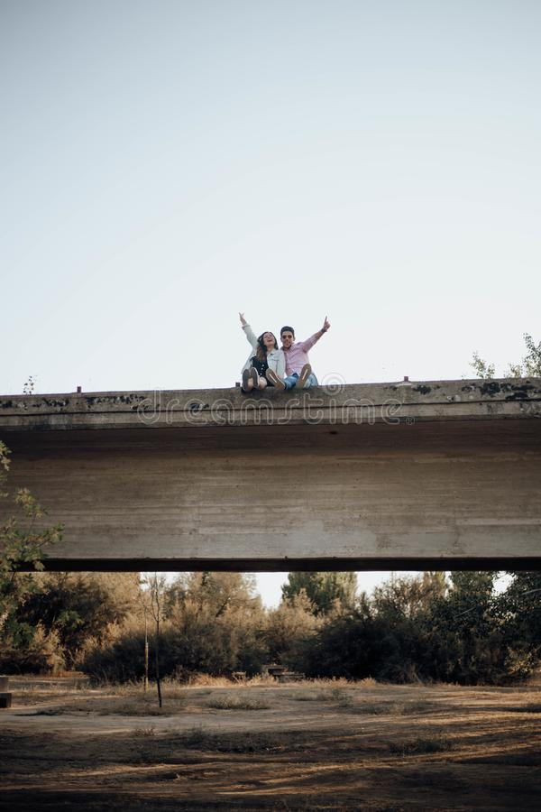 Young couple in love raising their hands on an old bridge stock photography