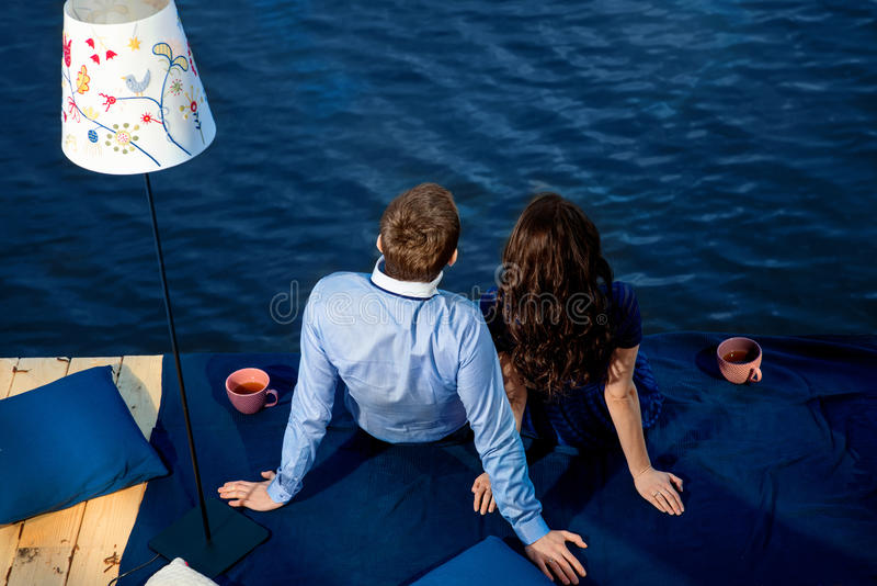 Young couple in love relaxing on terrace near water. Young couple in love relaxing on terrace near blue water royalty free stock photo