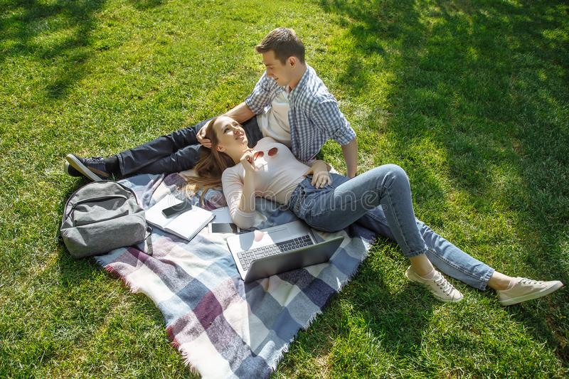 Young couple in love resting on the lawn after study stock photos