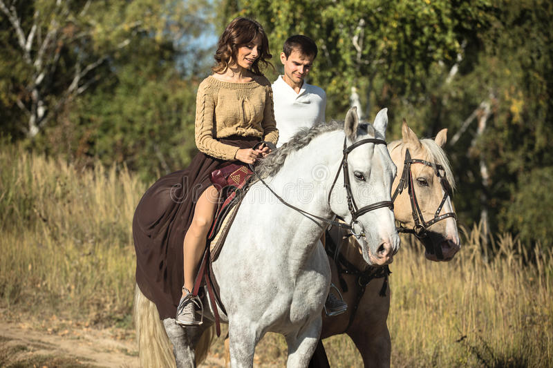 Young couple in love riding a horse. Walking on the background of autumn nature in a beautiful field royalty free stock photography