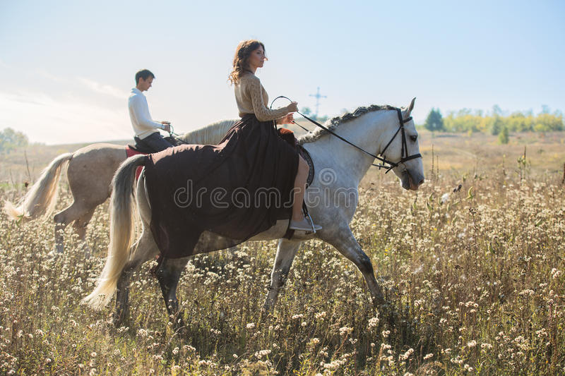 Young couple in love riding a horse. Walking on the background of autumn nature in a beautiful field royalty free stock image