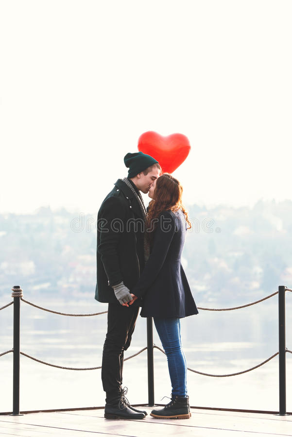 Young couple in love, at the riverside, with a red balloon royalty free stock photography