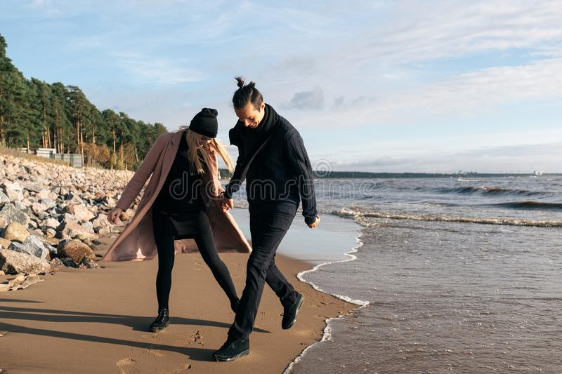 Young couple in love run away from waves. Happy lovers have fun on the beach royalty free stock image