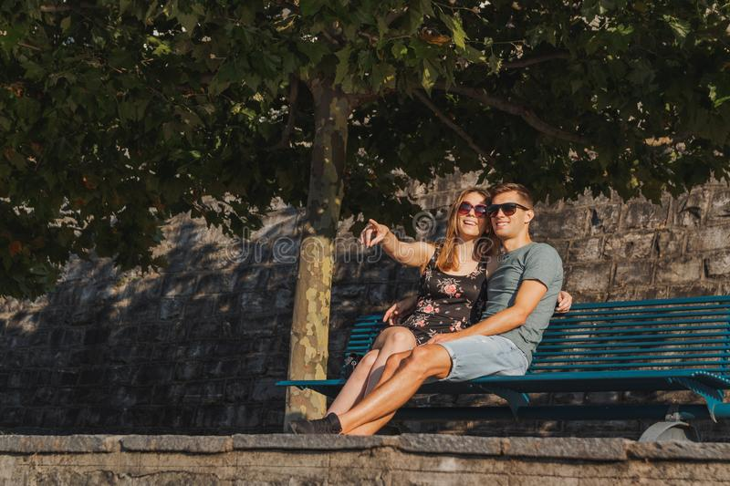 Young couple in love seated on a bench and relaxing during a sunny day royalty free stock photos