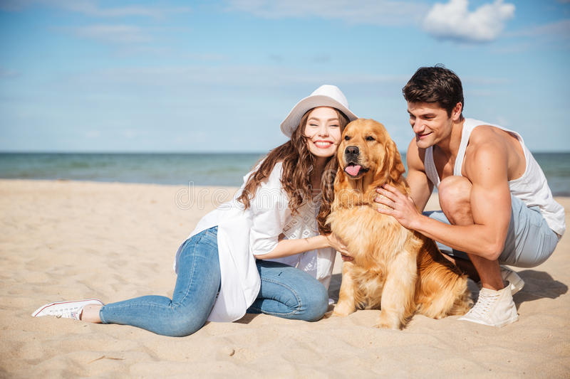 Young couple in love sitting on the beach with dog royalty free stock images