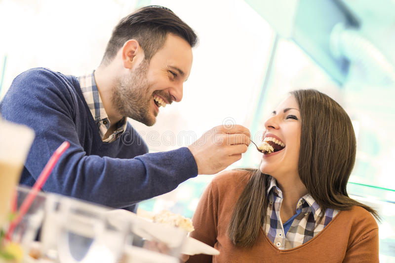 Young couple in love sitting in a cafe,eating cake royalty free stock images