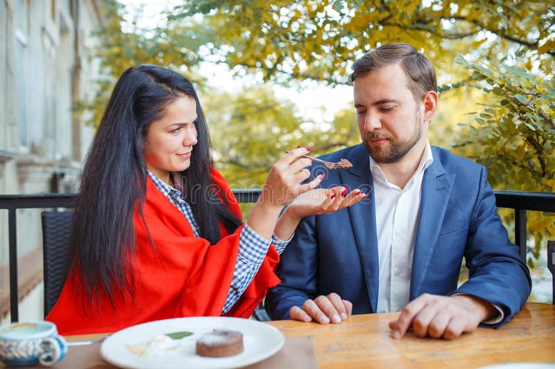 Young couple in love is sitting in cafe and woman is feeding cake her man. stock image