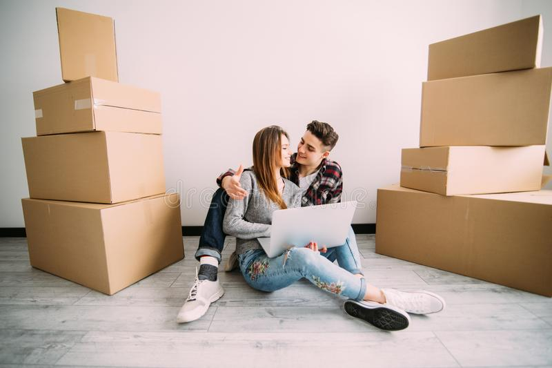 Young couple in love sitting on the floor of their new apartment, planning redecoration and searching for ideas on a laptop comput royalty free stock photography