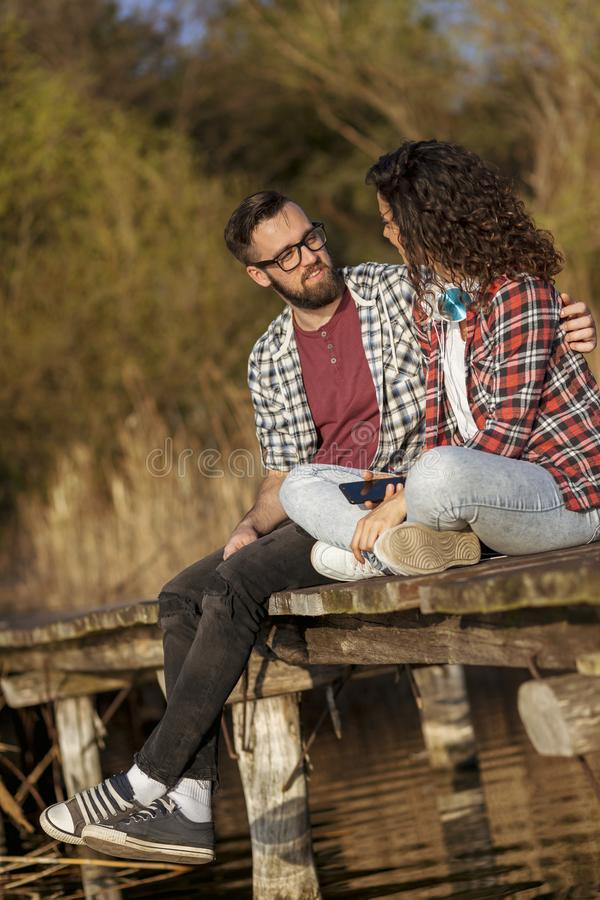 Couple sitting at the lake docks stock images