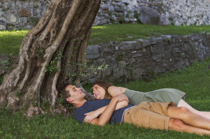 Young Couple in Love sitting under a tree in a castle royalty free stock photography