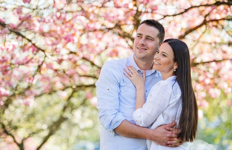 Young couple in love standing outside in spring nature. royalty free stock photos