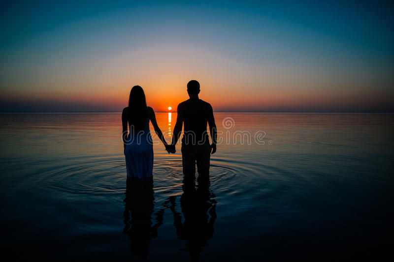 Young couple in love at sunset royalty free stock photography