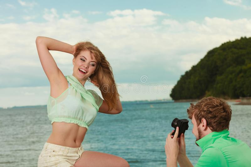 Young couple in love is taking photos on sea pier royalty free stock images