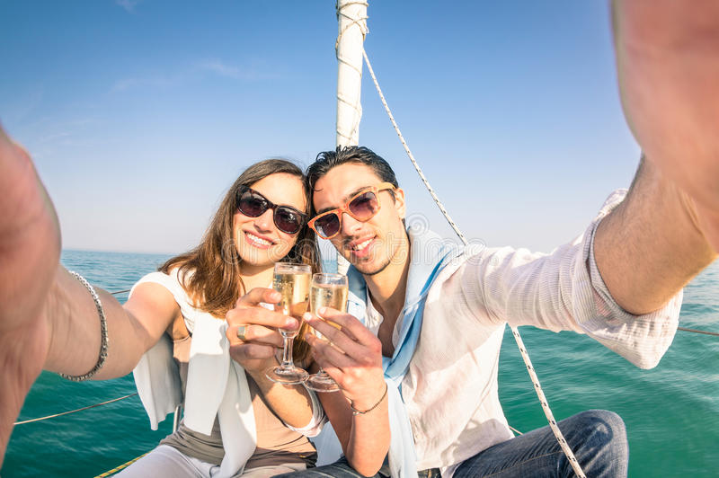 Young couple in love taking selfie on sailing boat. Cheering with champagne wine - Happy jubilee party cruise travel on luxury sailboat with boyfriend and stock image