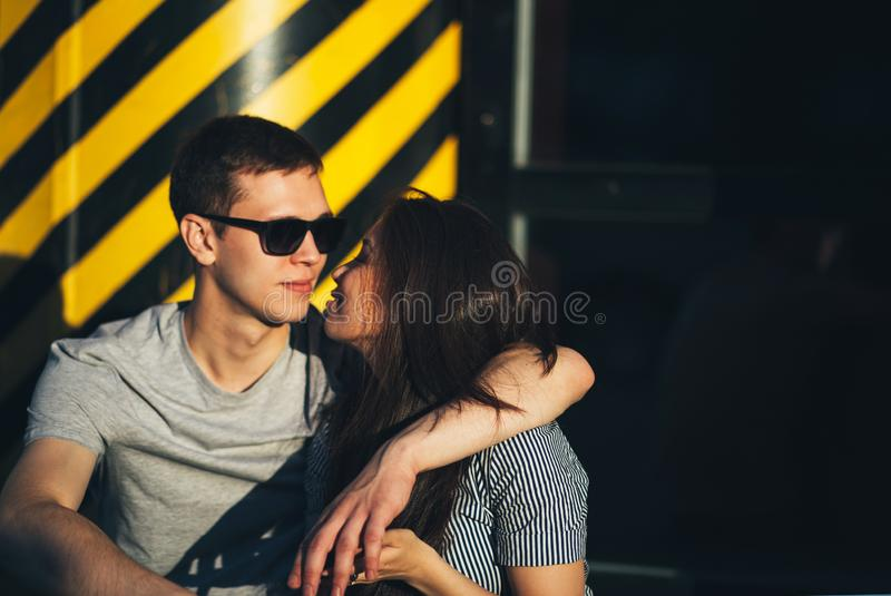 Young couple in love teenagers dressed in casual style sitting together on city street royalty free stock images