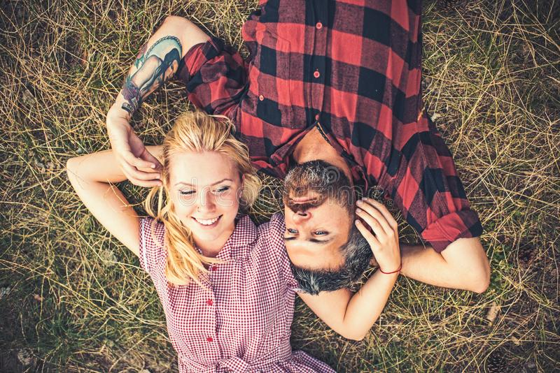 Young couple in love. Two people lying on green grass. Girlfriend and boyfriend playing with each others hair stock image
