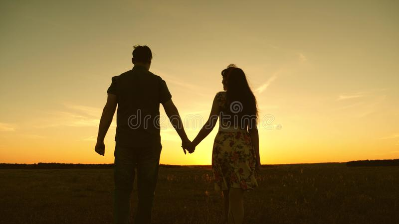 Young couple in love walking across the field holding hands. girl and man go to the sunset. happy family walks in the stock photos