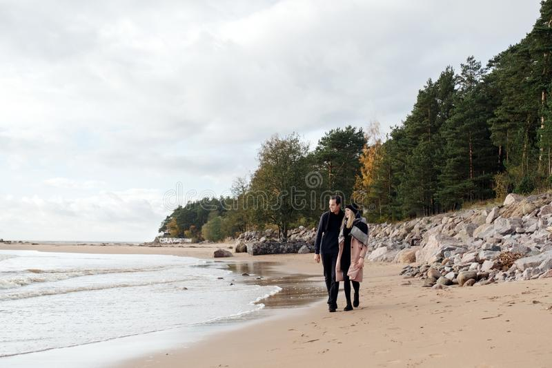 Young couple in love walking on the beach coast. Cold autumn weather, trees in the background. royalty free stock photography