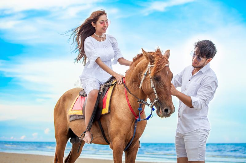 Young couple in love walking with the horse at sea beach on blue sky . honeymoon tropical sea summer vacation. bride groom on the royalty free stock images