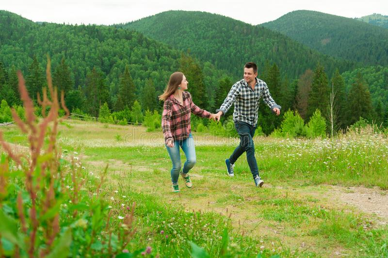 Young couple in love walking in mountains. Lovely happy couple have fun outdoors. Young couple in love walking in mountains. Portrait of a happy couple laughing royalty free stock image