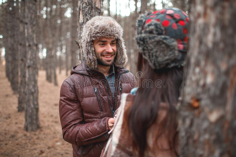 Aouple in love, warmly dressed are in a cold autumn forest and have fun there. royalty free stock photography