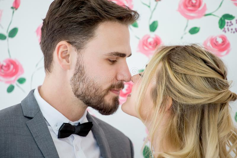young couple in love Wedding Bride and groom kissing on roses backdrop. Newlyweds. Closeup portrait of a beautiful having a royalty free stock image