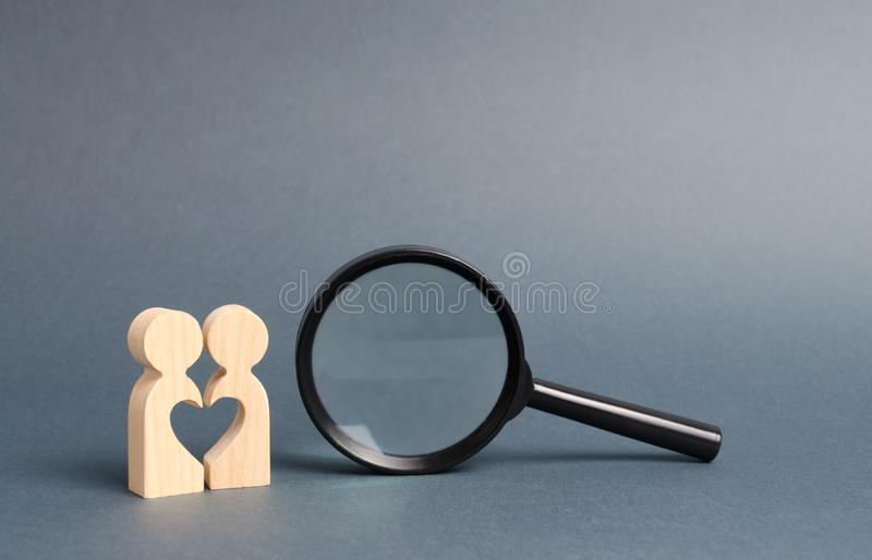 A young Couple of lovers of lovers are standing near to a magnifying glass. Declaration of love and the creation of strong love. Relationships. concept of royalty free stock photography