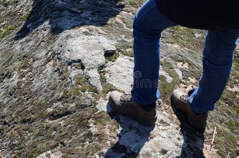 Male feet in boots.Climber on the top of rock.Relaxation after long walk. Young couple loves climbing and active life,stoped to relax after long way hiking.Male stock photo