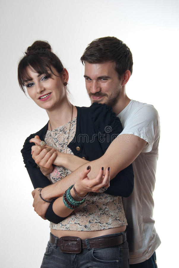Young couple in loving embrace. Attractive young couple in loving embrace with the men hugging the women tightly from behind stock images